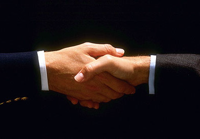 handshake between two well dressed business men