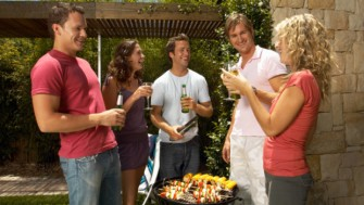 Young women and men holding drinks standing around bbq