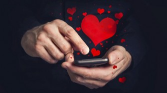 Man typing love text messages on a smartphone for Valentine's