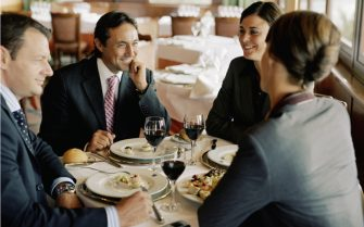 Two businessmen and women at restaurant table, laughing