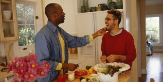 Gay man feeding partner in kitchen